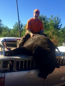Cody Brown poses with the 695-pound bear he killed near Kenansville on Nov. 11.